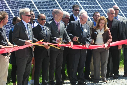 Paul Lingle; Raj Rao, president and CEO of IMPA; Mayor Dave Snow; Randy Baker, general manager of Richmond Power & Light; and Misty Hollis, chair of the RP&L board, cut a ribbon during a ceremony at the Richmond 2 solar park.