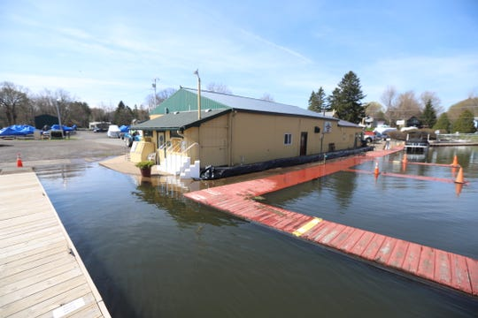 Water laps against docks at Arney's Marina at Sodus Point, which has set out sandbags.