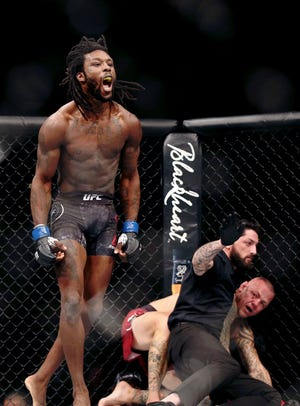 Desmond Green (blue gloves) celebrates his win over Ross Pearson (red gloves) during UFC Fight Night at Wells Fargo Arena in Philadelphia on March 30. Green, a Rush-Henrietta graduate, is scheduled to fight in Rochester on Saturday night.