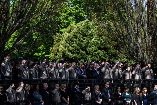 Members of Cowlitz County law enforcement stand at attention at the funeral procession for Cowlitz County Sheriff's Deputy Justin DeRosier.