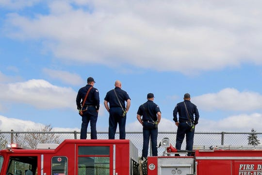 Firefighters watch the funeral procession for Cowlitz County Sheriff's Deputy Justin DeRosier from a Vancouver, Washington, overpass.