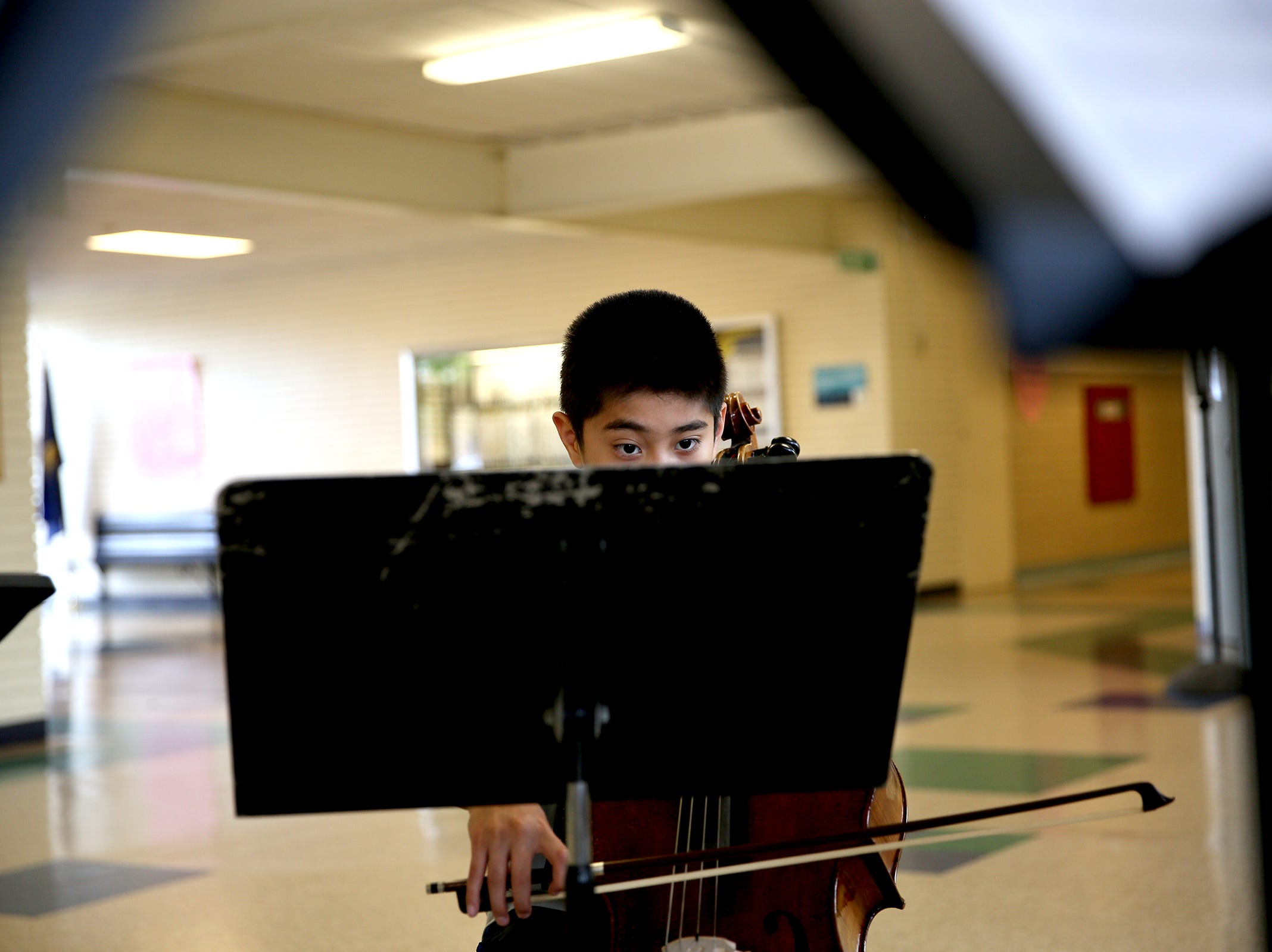 Sixth grade student, Ivan Rodriguez, reads sheet music while practicing his cello during practice at Waldo Middle School on April 19, 2019.