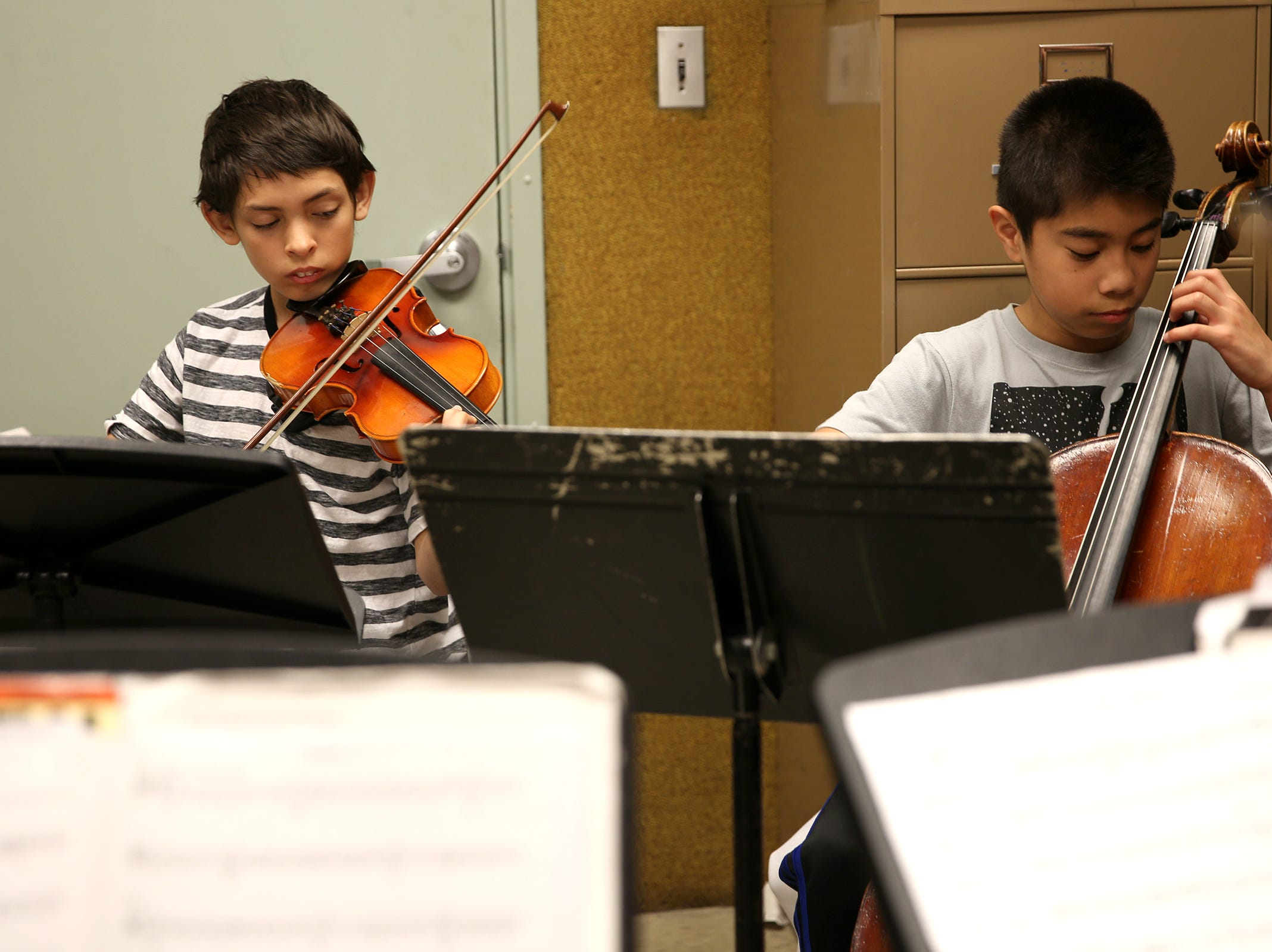 Seventh grade student Kaden Sherwood and sixth grade student Ivan Rodriguez participate through the Music Lessons Project, which offers private or small group lessons to students in Title I schools, at Waldo Middle School on April 19, 2019.