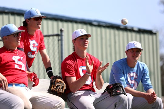 South Salem High School baseball player Ryan Brown (throwing ball) hangs out at practice with his teammates at Gilmore Field in Salem on April 24, 2019.