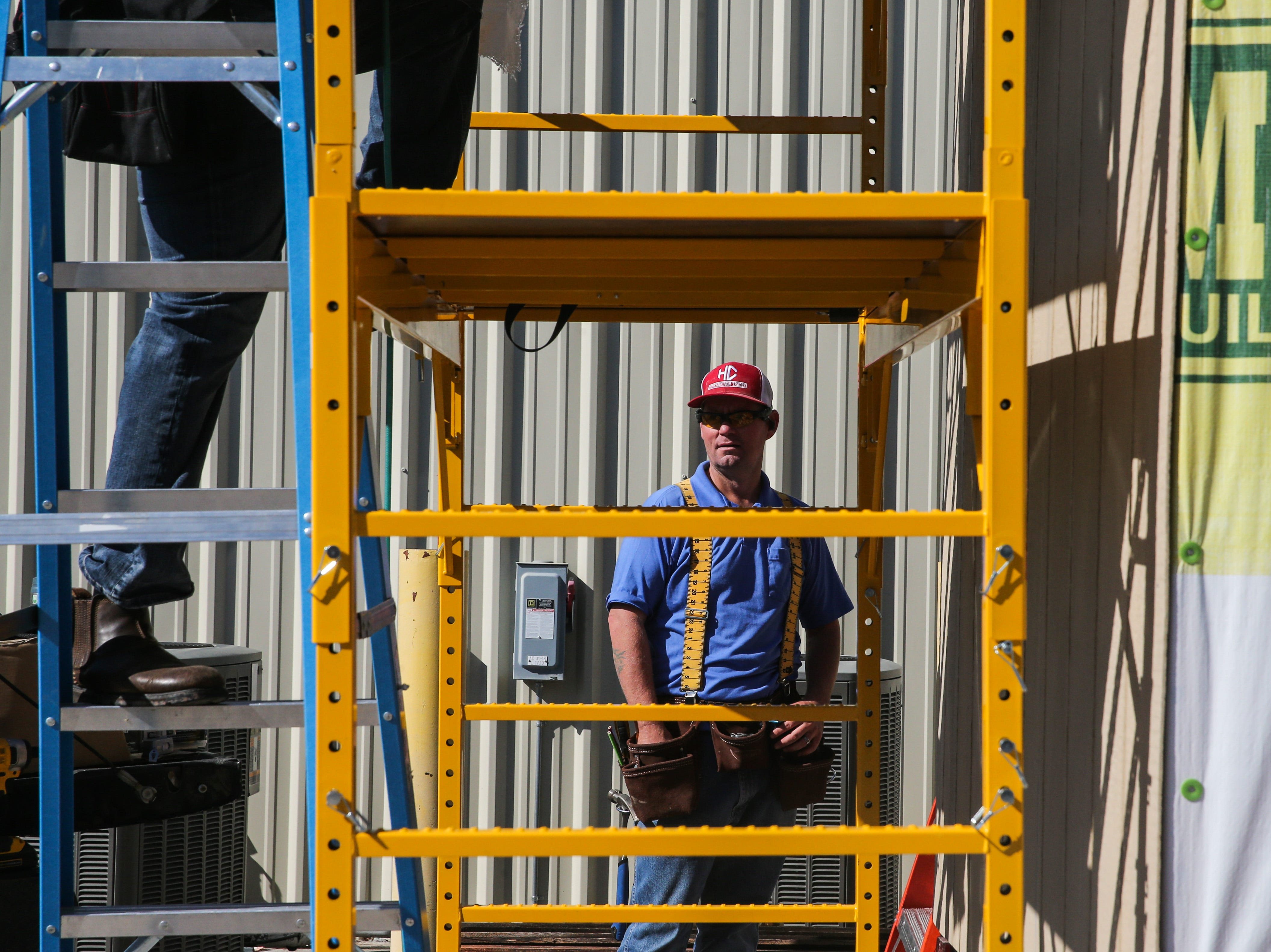Casey Armor looks on as other students put up a panel on a tiny house project Thursday, April 25, 2019, at Howard College.