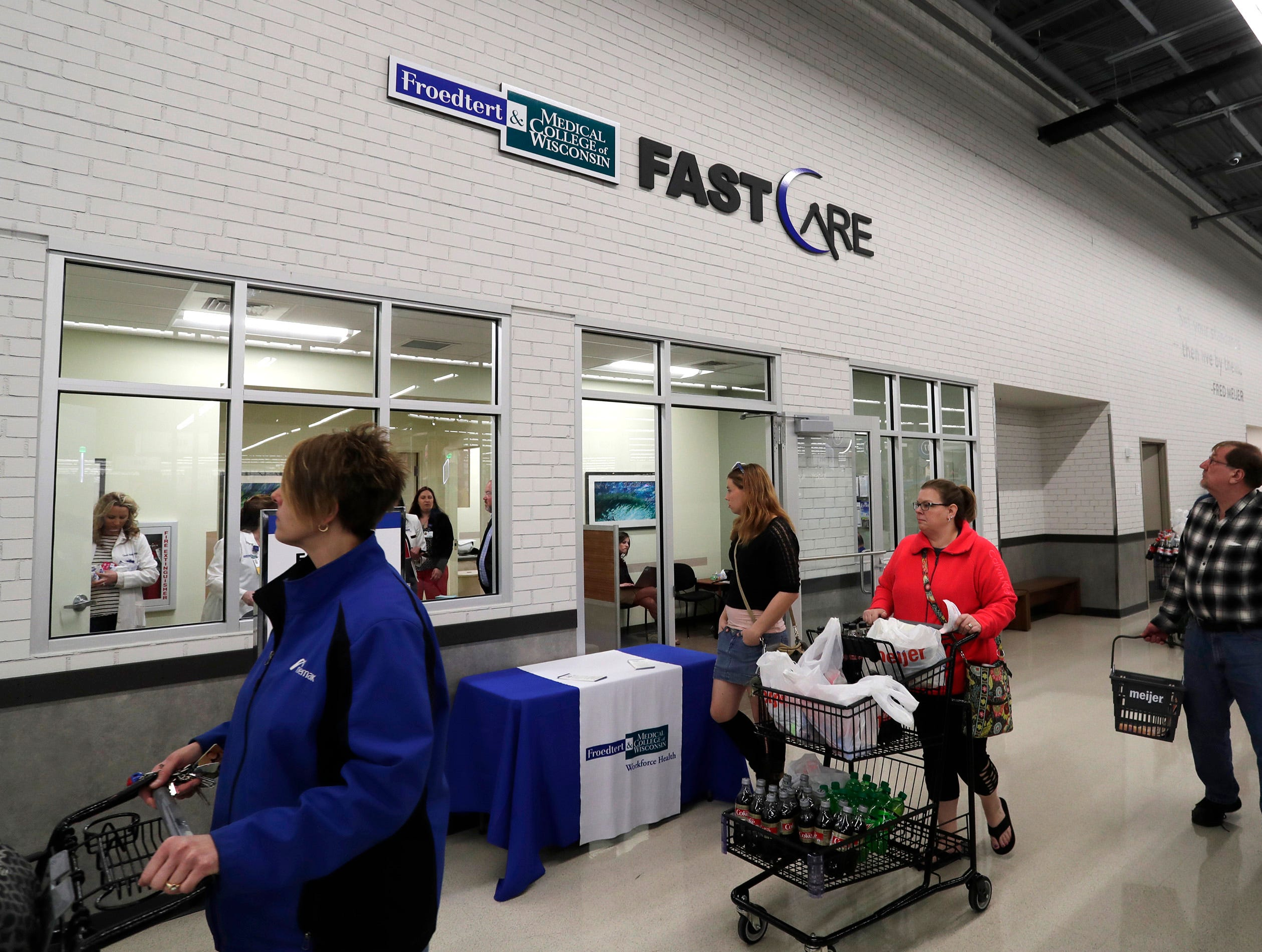 People walk past the Froedtert Fast Care at Meijer, Thursday April 25, 2019, in Sheboygan, Wis. The 155,000-square-foot supercenter has 300 employees on opening day.