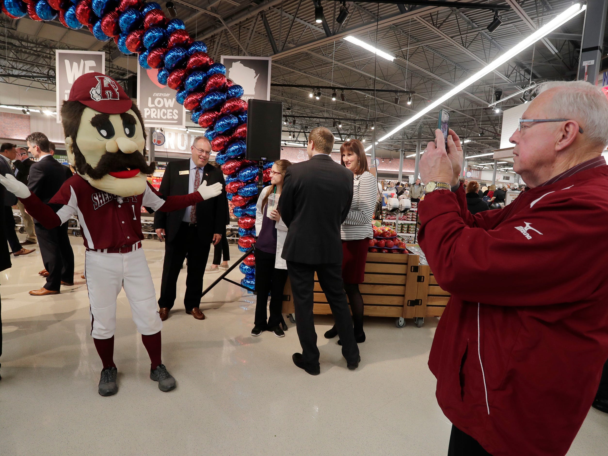 Sheboygan A's No. 1, left, poses for Denny Moyer during the grand opening festivities at Meijer, Thursday April 25, 2019, in Sheboygan, Wis. The 155,000-square-foot supercenter has 300 employees on opening day.