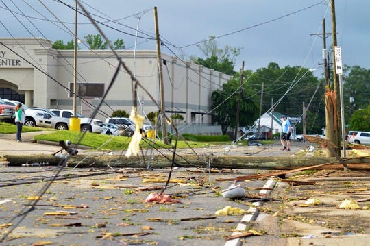Residents walk around downed utility poles Thursday morning in Ruston, near exit 85 off Interstate 20.