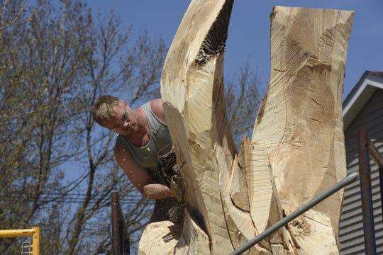 Jarrett Dahl carves a tree using a chainsaw on April 24.