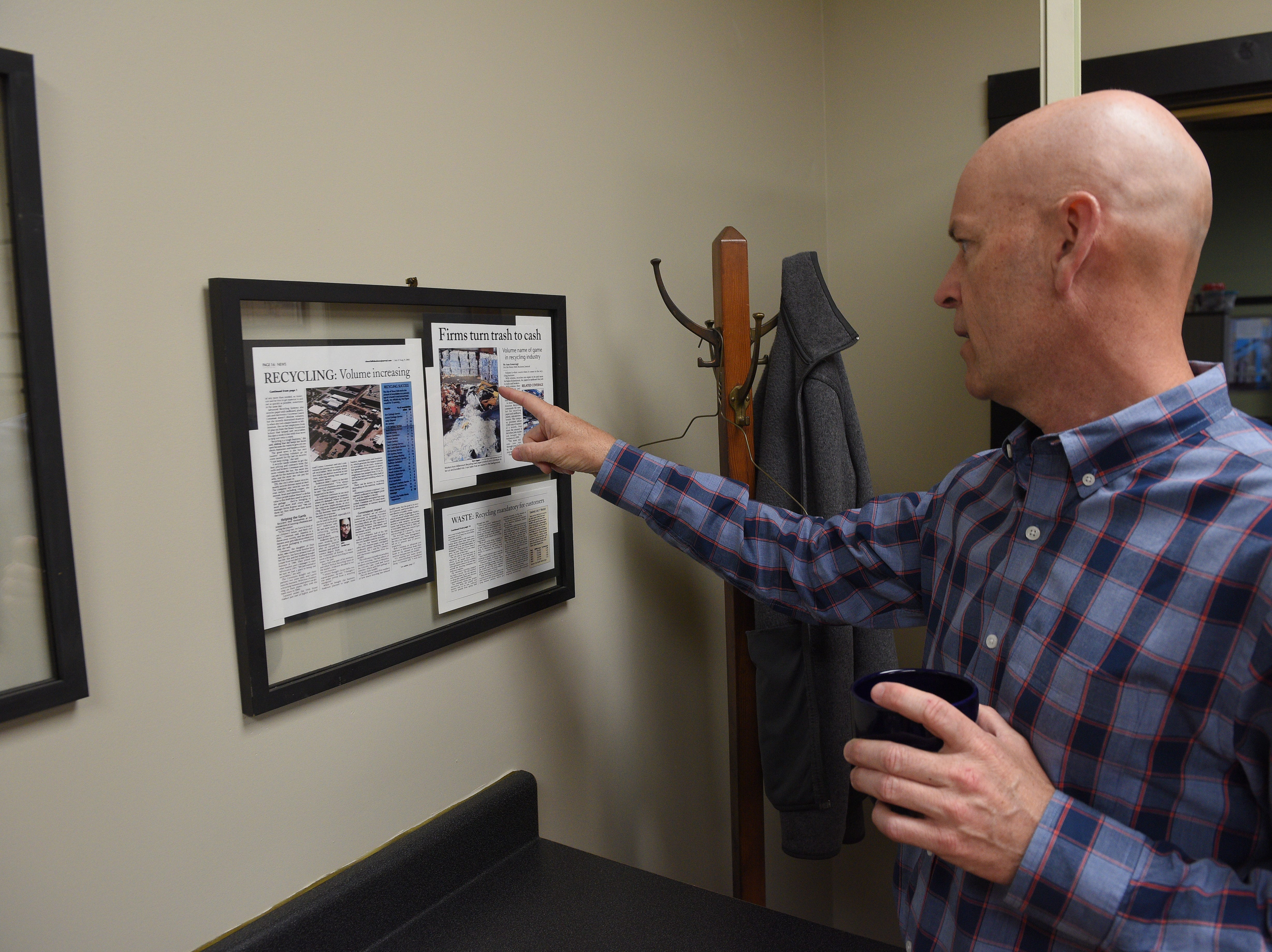 Millennium Recycling Founder and CEO Jake Anderson looks at old newspaper clippings about his business' earlier days. Millennium is celebrating its 20th anniversary this year.