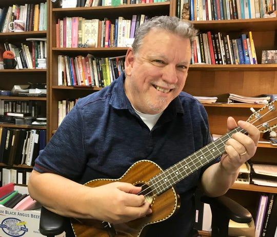 International ukulele champion Richard Maxson plays his award winning song in his office at Drury University.