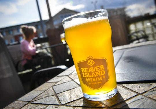 A freshly poured glass of Tangerine American Wheat beer is served on the patio as the sun shines Wednesday, April 24, at Beaver Island Brewing Co. in St. Cloud.