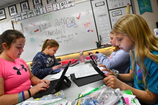 Fifth grade students gather to research their group project on homelessness Thursday, April 25 at Rice Elementary School. The school is one of 24 in the state authorized to teach the International Baccalaureate Primary Years Programme.