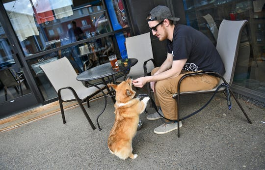 Chris Dilley gives his dog Newton a treat while enjoying a spring seasonal beer on the patio Wednesday, April 24, at Beaver Island Brewing Co. in St. Cloud.