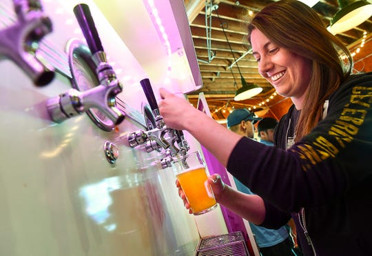 Ally Teclaw pours a glass of Tangerine American Wheat Wednesday, April 24, at Beaver Island Brewing Co. in St. Cloud.