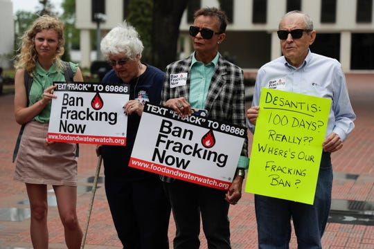 Activists hold signs during a rally held to urge Gov. Ron DeSantis to stick to a campaign promise he made to ban fracking in Florida.