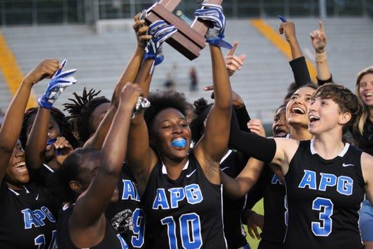 Godby senior Kiara Byrd (10) holds up the district championship trophy after the Cougars' flag football team beat Lincoln 19-6 during the district final at Gene Cox Stadium on April 24, 2019.