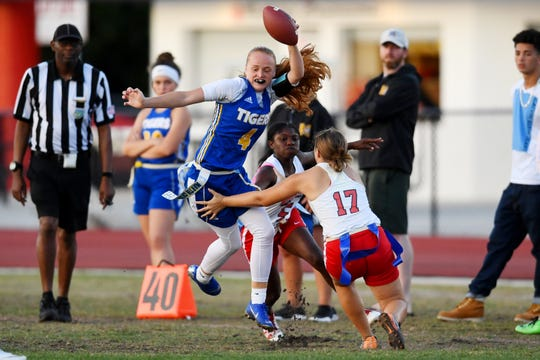 Martin County High School's Elise Liggett (4) tries to avoid the defense of St. Luce West Centennial's Paris Newton (5) and Emily Walker (17) during the District 4-2A flag football championship game on Wednesday, April 24, 2019 hosted by South Fork High School. Martin County blanked St. Lucie West Centennial 25-0 to claim the title.
