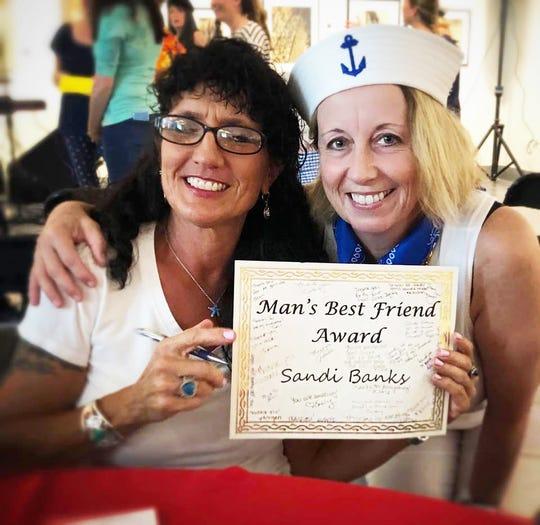 Heidi Fischer, left, and Sandi Banks show off the Man's Best Friend Award.