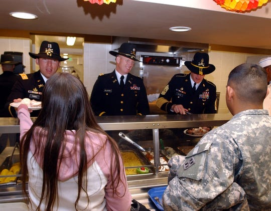 Spc. Nickolias Sauceda and his wife, both Michigan natives, are served a Thanksgiving meal by, from left, Capt. Michael Forbes, Lt. Col. Monty Willoughby, and Command Sgt. Maj. Miles Wilson at the Striker Cafe in Fort Carson, Colorado.