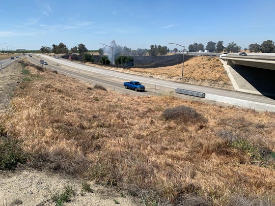 A grass fire just north of Highway 198 disrupts traffic on Thursday, April 25, 2019.
