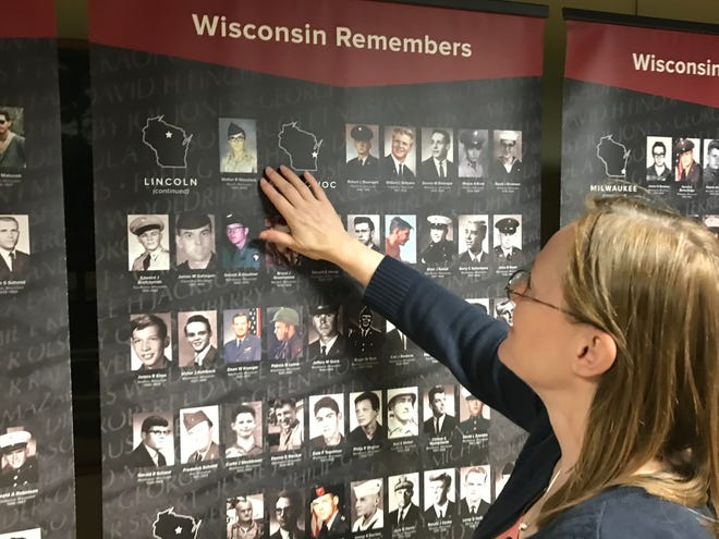 """Kathy Volkmann, the curator of artifacts for the Marathon County Historical Society, looks at the picture of Pfc. Walter Waschick. His photo is part of the """"Wisconsin Remembers: A Face for Every Name"""" exhibit now on display in the Woodson History Center in Wausau."""