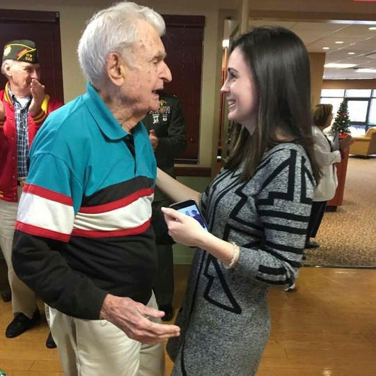 In this December 2017 photo provided by Beth Regan, Regan speaks to Robert Graham. The decorated World War II veteran who died in April 2017 with no living relatives is being honored thanks to an unlikely friendship with the young woman who is determined to give him a farewell befitting a hero. (AP Photo/Jim Regan)