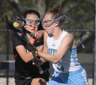 Mamaroneck's Mia Sheindlin (14) guards Suffern's Emma Muchnick (3) during girls lacrosse game at Suffern Middle School on April 24, 2019. Suffern defeats Mamaroneck 12-9.