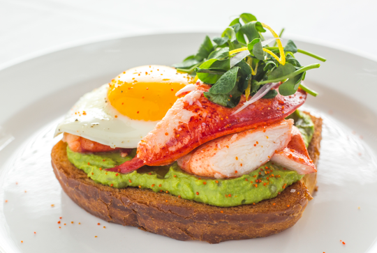 Lobster Toast with a sunny-side egg, avocado, sweet peas,  and preserved lemon at Ocean Prime in New York City.