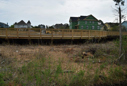 Wood shavings and tree stumps can be seen along the edges of the boardwalk that will serve as a road connection lots that average about $1 million in a private community north of Bethany Beach.