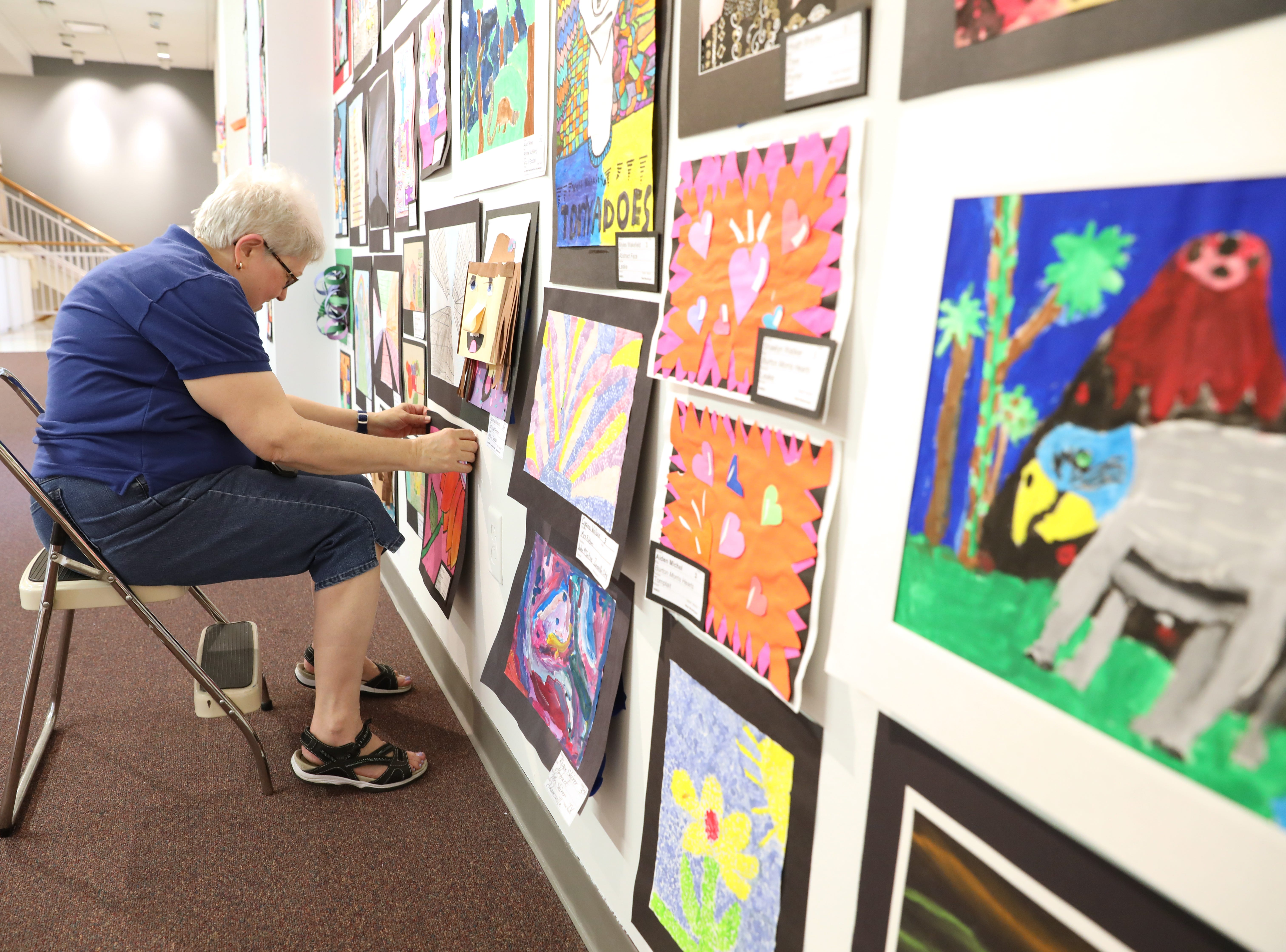 Brooke Anderson of the AAUW hangs art for the Muskingum County K-12 Student Art Exhibition at the Zanesville Museum of Art.