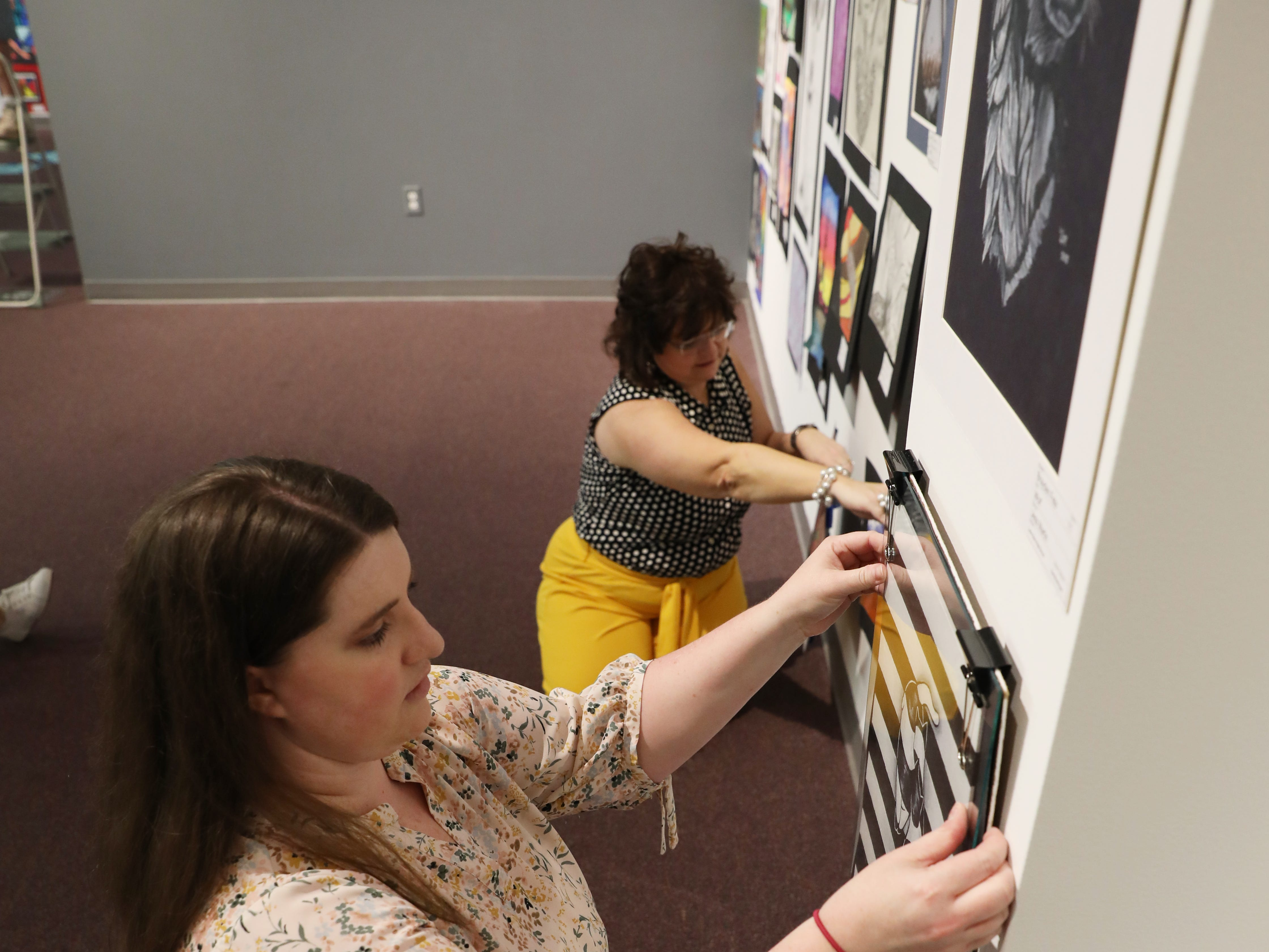 Sarah Franklin, Collections and Exhibitions Manager, and Peggy Gilchrist, a docent, hang art for the Muskingum County K-12 Student Art Exhibition at the Zanesville Museum of Art.