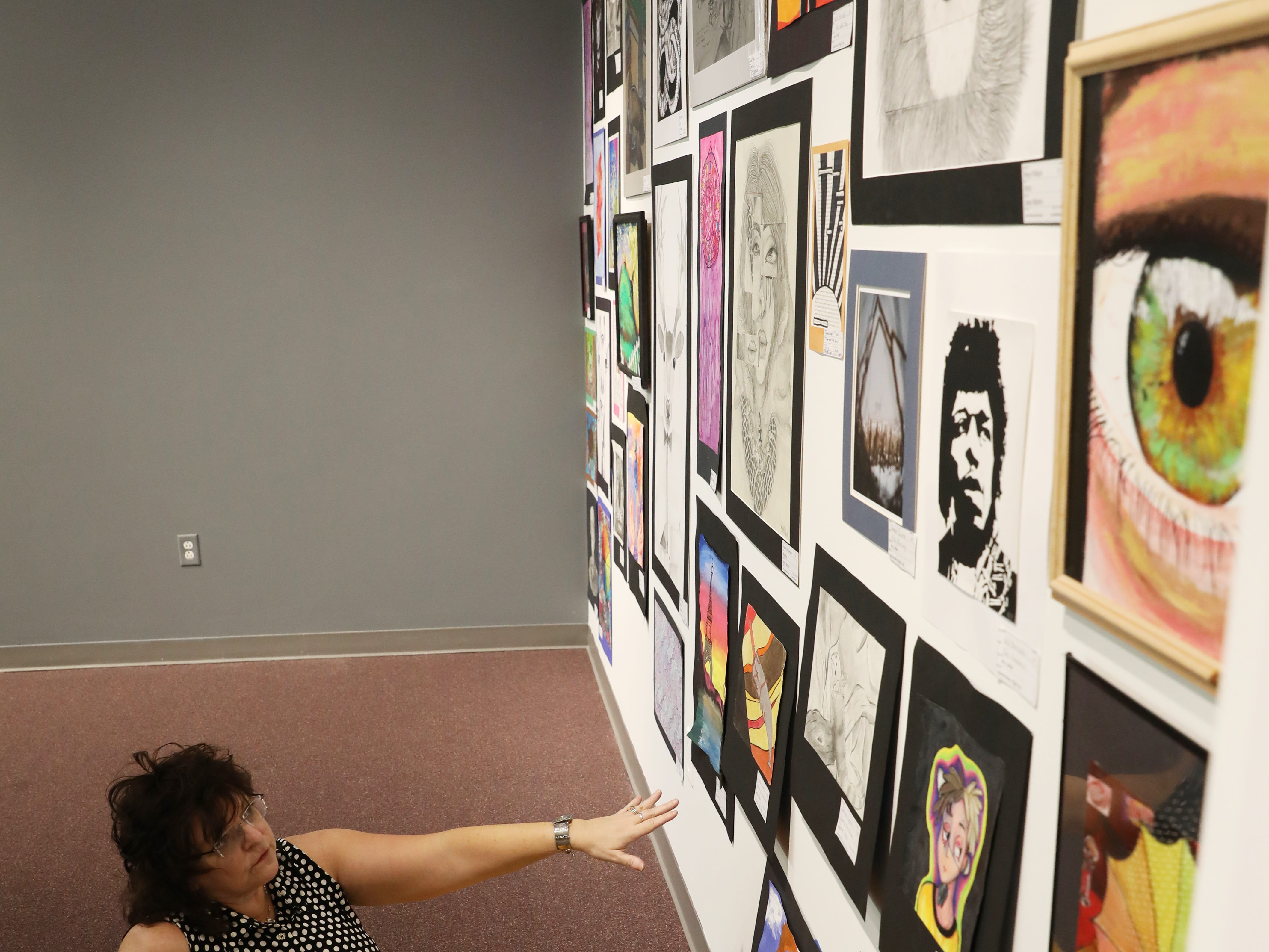 Peggy Gilchrist considers where to hang pictures while hanging art for the Muskingum County K-12 Student Art Exhibition at the Zanesville Museum of Art.