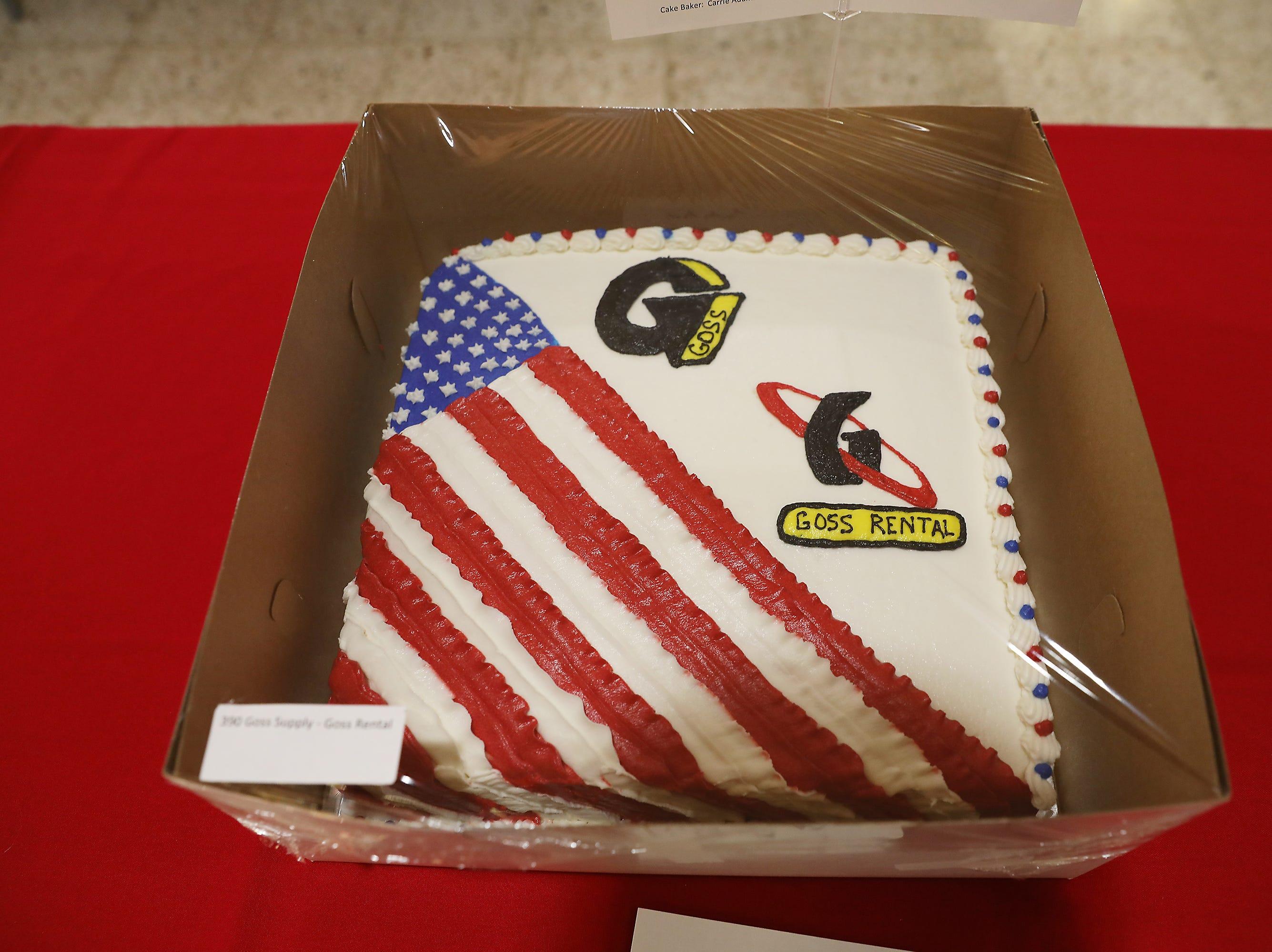 "4:45 P.M. Friday cake 390 Goss Supply Goss Rental - wooden 18"" x 35"" flag; $390"