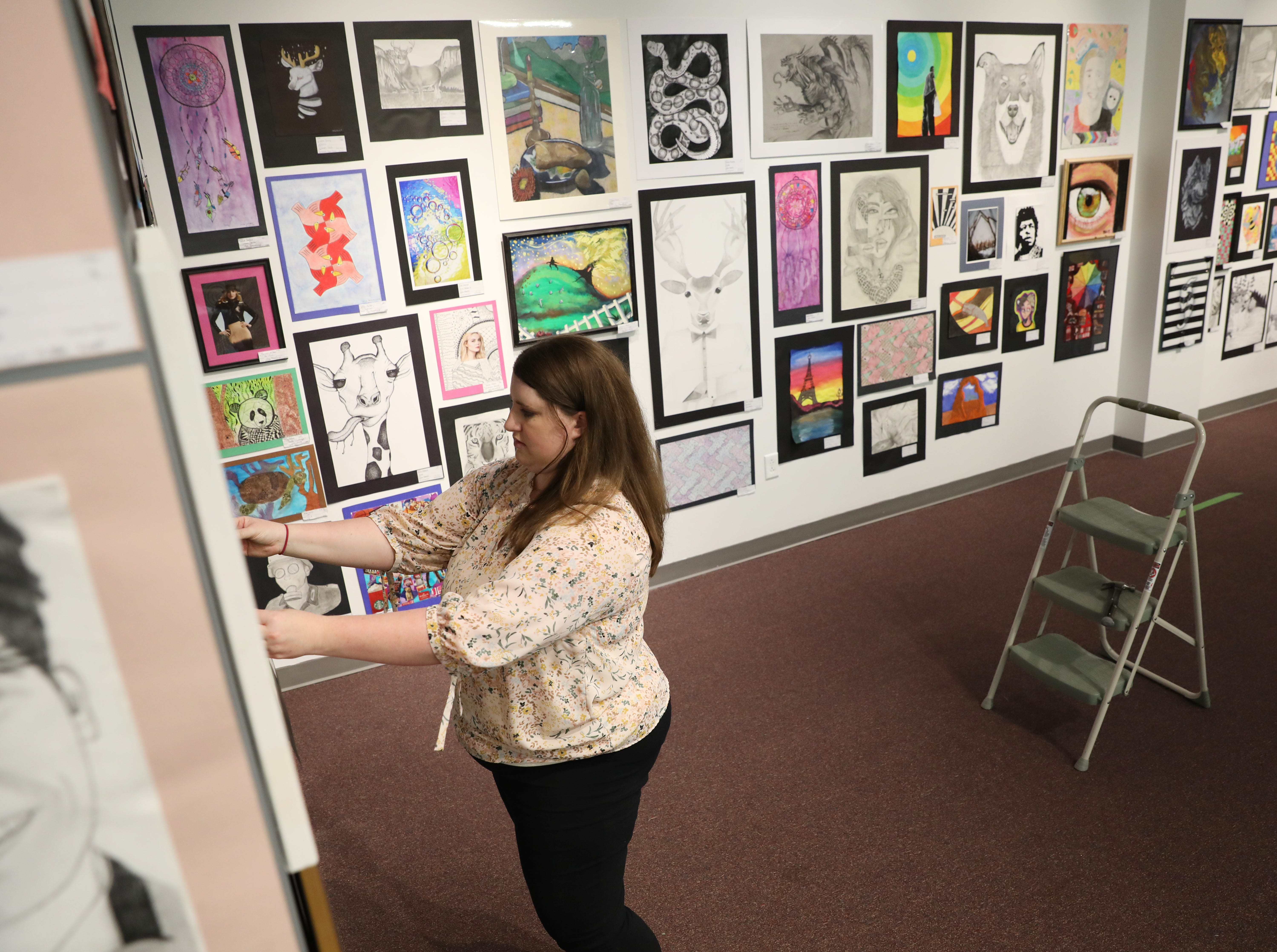 Sarah Franklin hangs a piece for the Muskingum County K-12 Student Art Exhibition at the Zanesville Museum of Art.