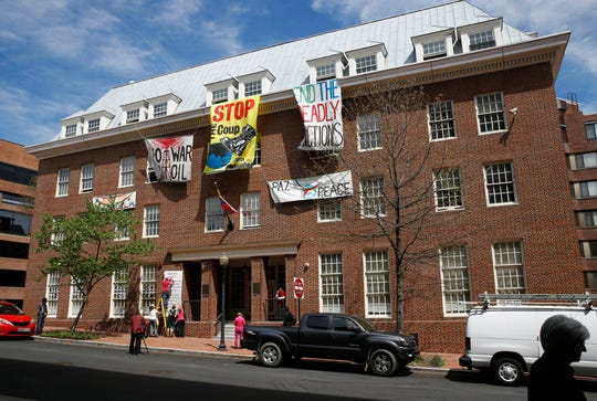 Activists' banners protesting against Juan Guiado, opposition leader and self-proclaimed interim president of Venezuela, hang outside the shuttered Venezuelan Embassy on April 24, 2019, in Washington, D.C.. Activists have been staging a round-the-clock protest inside the embassy, occupying it to prevent the Guiado opposition from taking over the building.
