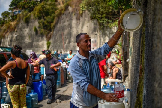 A man fills containers with water flowing down from the Wuaraira Repano mountain in Caracas, Venezuela, on March 13, 2019. Nationwide blackouts have been among many problems the strife-torn South American country has endured in recent years.