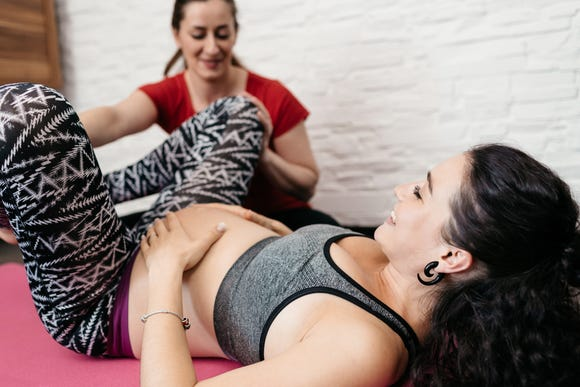 A pregnant woman laying on her back and practicing birthing positions with her doula at home.