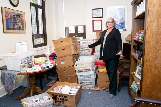 """Washington Senator Maureen Walsh on April 23, 2019, stands next to bins full of playing cards she received in the mail following her comments about nurses in rural areas possibly spending a """"considerable amount of the day"""" playing cards."""