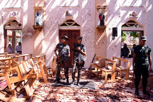Sri Lankan soldiers look on inside the St Sebastian's Church at Katuwapitiya in Negombo on April 21, 2019, following a fatal bomb blast during the Easter service. A series of eight devastating bomb blasts ripped through high-end hotels and churches holding Easter services in Sri Lanka on April 21, killing nearly 160 people, including dozens of foreigners.