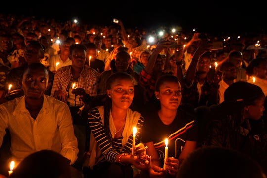Rwandans sitting in the stands hold candles as part of a candlelit vigil during the memorial service held at Amahoro stadium in the capital Kigali, Rwanda, April 7, 2019. Rwanda is commemorating the 25th anniversary of when the country descended into an orgy of violence in which some 800,000 Tutsis and moderate Hutus were massacred by the majority Hutu population over a 100-day period in what was the worst genocide in recent history.