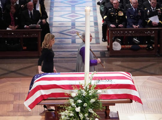 Jenna Bush Hager touches the flag-draped casket of her grandfather, former President George H.W. Bush during his state funeral on Dec. 5, 2018.