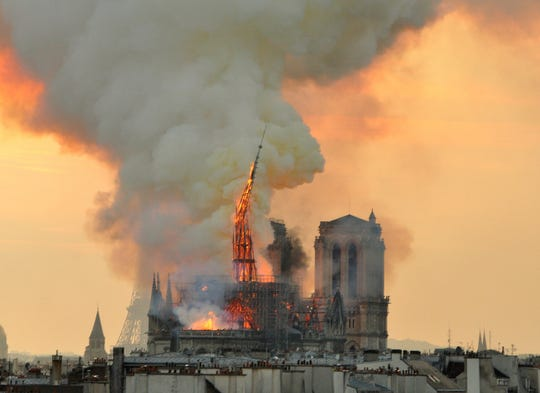 """Flames and smoke rise from the blaze as the spire starts to topple on Notre Dame cathedral in Paris, April 15, 2019. An inferno that raged through Notre Dame Cathedral for more than 12 hours destroyed its spire and its roof but spared its twin medieval bell towers, and a frantic rescue effort saved the monument's """"most precious treasures,"""" including the Crown of Thorns purportedly worn by Jesus, officials said."""