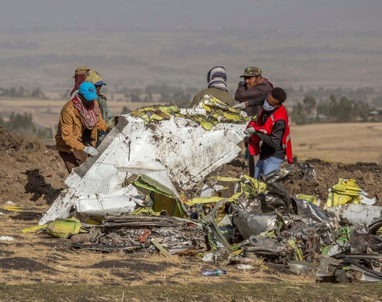 Rescuers work at the scene of an Ethiopian Airlines flight crash near Bishoftu, south of Addis Ababa, Ethiopia, March 11, 2019. A spokesman says Ethiopian Airlines has grounded all its Boeing 737 Max 8 aircraft as a safety precaution, following the crash of one of its planes on March 10 in which 157 people were killed.