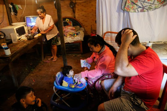 The Gutierrez family, diplaced by floods, prepare for breakfast in a temporary shelter in Asuncion, Paraguay, Friday, April 5, 2019.