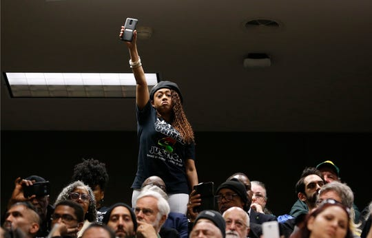 Jamilia Land, a friend of the family of police shooting victim Stephon Clark, holds up a cell phone during a hearing on legislation to restrict the use of deadly force by police, Tuesday, April 9, 2019, in Sacramento, Calif. Sacramento Police officers mistook the cell phone Clark was holding for a gun when he was shot and killed in 2018.