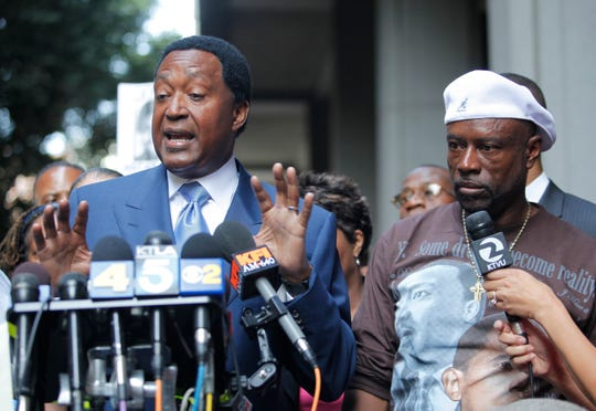 "In this 2010 photo, John Burris, left, the Oscar Grant family attorney, and Cephus ""Uncle Bobby"" Johnson, right, express their disappointment outside a Los Angeles court after a jury found BART police officer Johannes Mehserle only guilty of involuntary manslaughter of Grant while he laid on his stomach on an Oakland train platform."