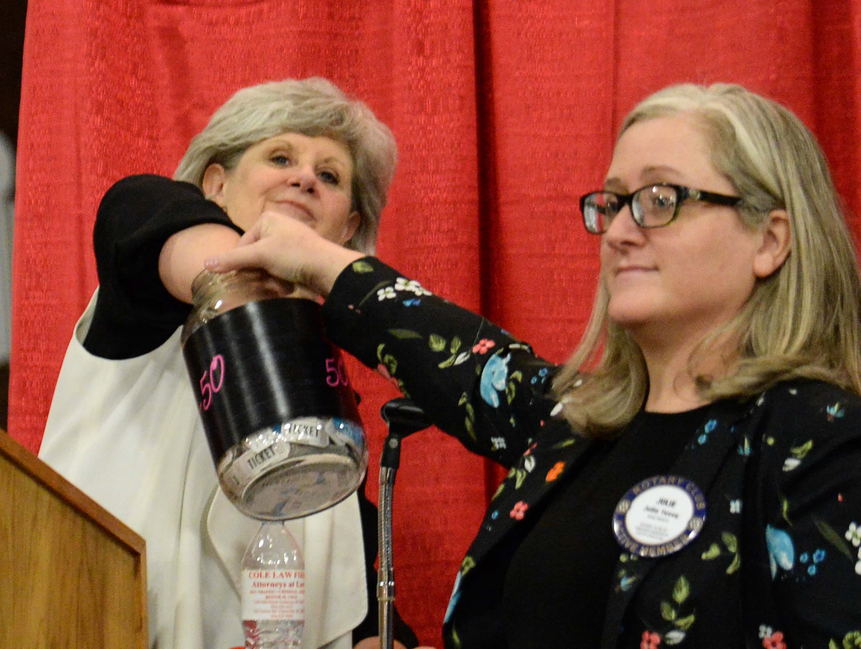 "Carole Burdette, left, mistress of ceremonies, picks a raffle ticket out of a jar held by Julie Tovey during the 13th Dancing For Our Heroes event with the theme ""Welcome to Las Vegas"" at the Civic Center of Anderson Thursday."