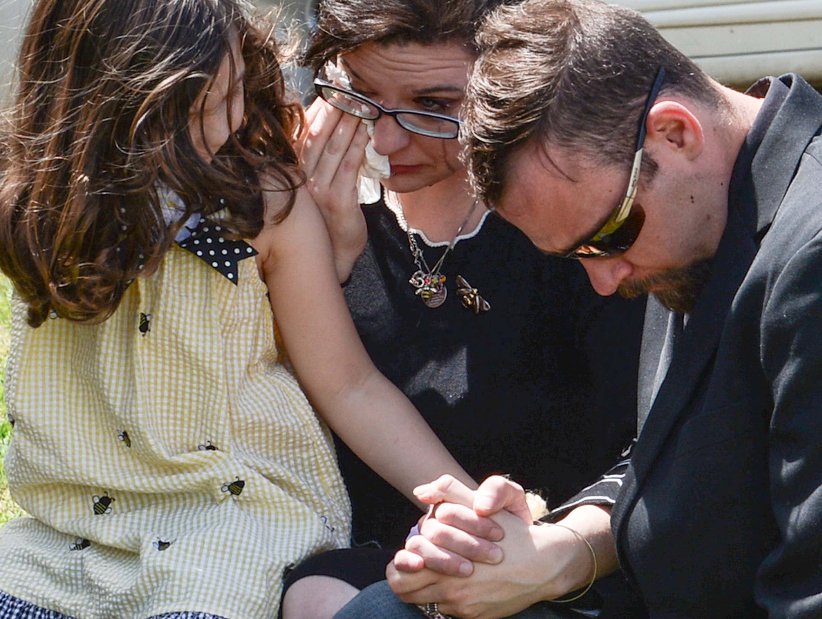 "Gracie Hess, left, hold the hand of her mother Ravyn Hammond, middle, and Cody Hess, right, as Rev. Kenny Owens of Westminster First Baptist Church offers an opening prayer, during an office dedication of the Foothills Alliance Oconee County Gwynnie Bee House in Walhalla Friday. Foothills Alliance, who with partners provides education, advocacy, and treatment services to prevent sexual assault trauma and child abuse services in Anderson and Oconee Counties, branched out from their Anderson office with an office in Walhalla last August. Hammond lost her daughter Gwynne Ann-Marie Hess, ""Gwynnie Bee, in 2017 from child abuse, and the office was renamed after her Friday in the presence of family, law enforcement, Sen. Thomas Alexander, Oconee County Sheriff Michael Crenshaw, and Tenth Circuit Solicitor David Wagner."