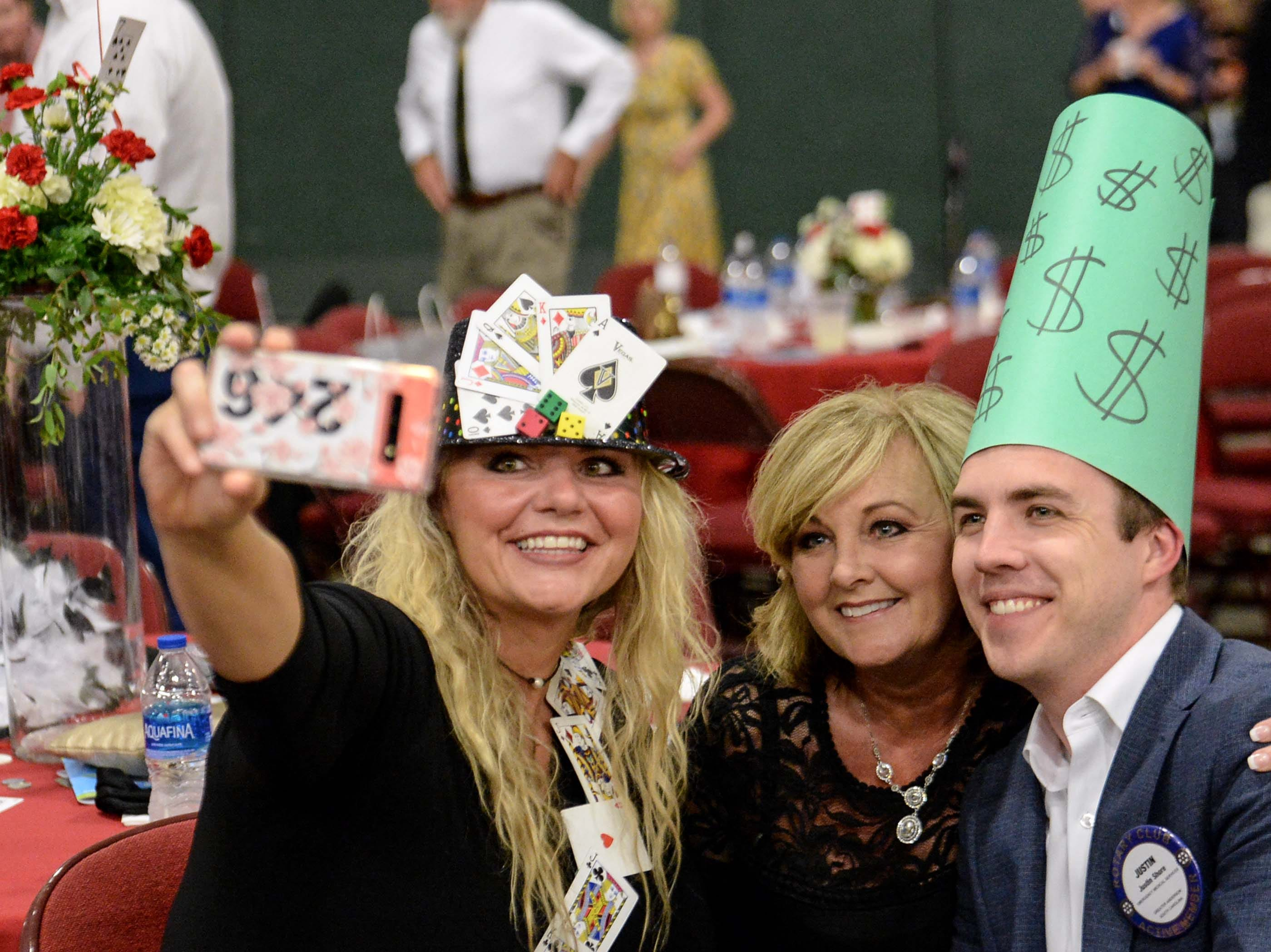 "Tina Scott, left, gets a selfie photo with Sherri Buchanan, and Justin Shore during the 13th Dancing For Our Heroes event with the theme ""Welcome to Las Vegas"" at the Civic Center of Anderson Thursday."
